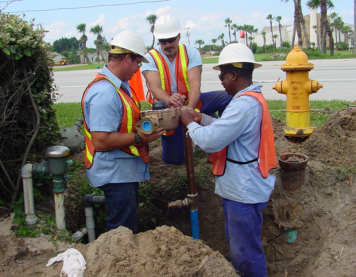 A water distribution crew works on a pipe in a ditch.