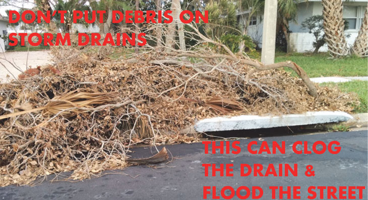 Image showing storm debris stacked on top of a storm drain. Do not do this. Debris can wash into the storm drain and clog it.