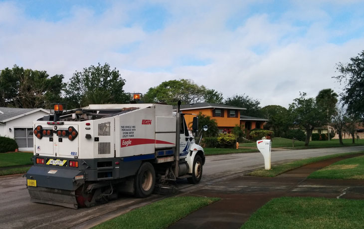 Street sweeper sweeping a roadway in Melbourne, FL.