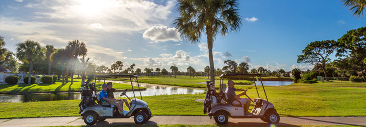 People driving golf carts on a sunny day on the golf course