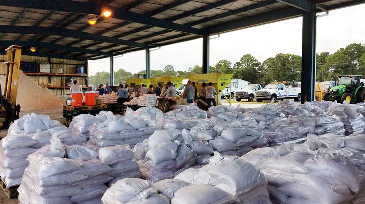 Piles of sandbags on pallets with crews working in the background to fill more for residents ahead of Hurricane Dorian.