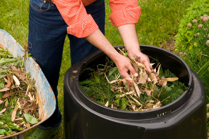 Someone adds leaves to a backyard composter. Photo by Metro: oregonmetro.gov