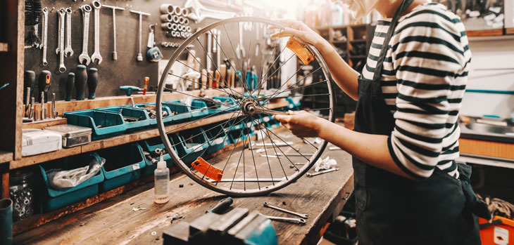 Woman holding a bicycle tire in a workshop. PHoto by iStock.