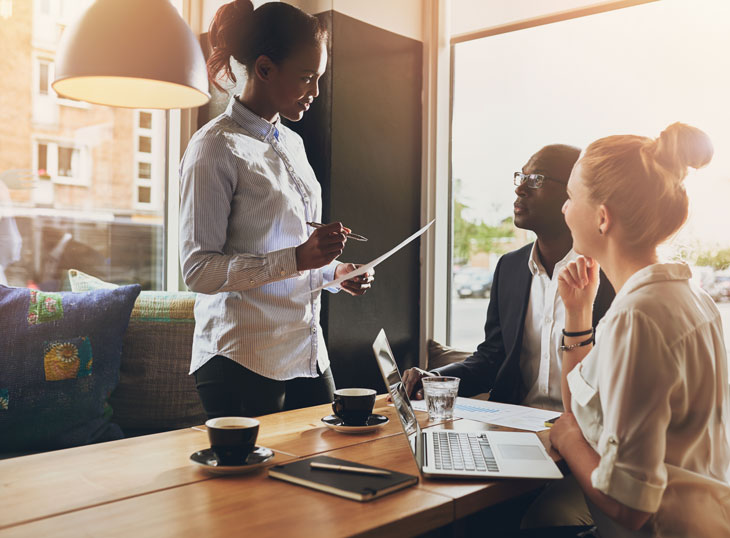 Two women and a man having a business meeting. Canva stock photo.
