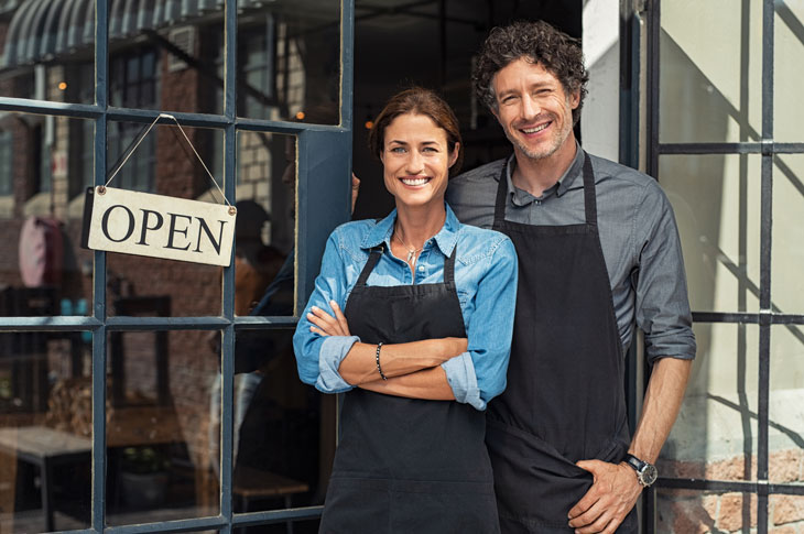 "A man and woman in aprons stand smiling next to an ""open"" sign. Canva stock photo."